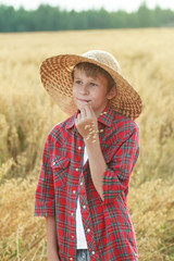 Teenage farm boy in wide-brimmed hat and oat cereal ears straw