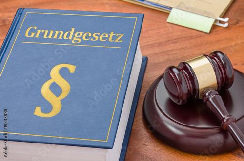 Leinwanddruck Bild Gesetzbuch mit Richterhammer - Grundgesetz