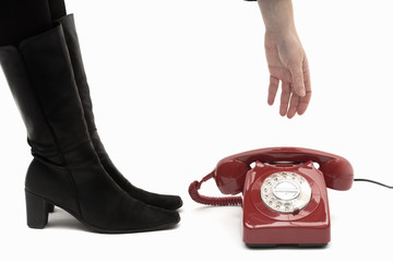 Woman picking up classic telephone on the floor