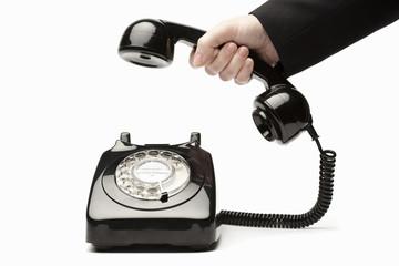 Female hand picking up retro black phone