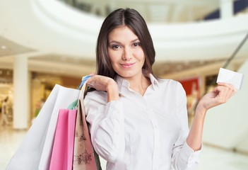 Card. Young beautiful woman holding shopping bags and a credit