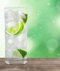 Vodka. Cocktail with ice and lime slice isolated on white