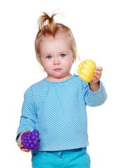 little girl holding toys fruits