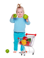 little girl with shopping trolley holding apples in hands