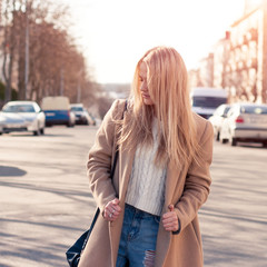 Amazing blonde girl walking alone on the road