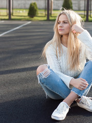 Young pretty fashionable blonde woman dressed in ripped jeans
