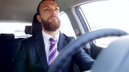 Serious business man listening music in car dancing