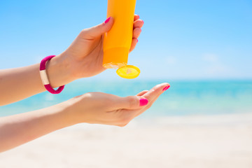 Woman pouring sunscreen in hand
