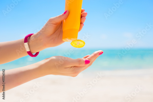 Woman pouring sunscreen in hand - 81536562
