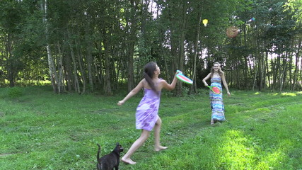 Happy pregnant mother with daughter play badminton game