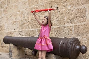 Niña con vestido rosa levantando paraguas rojo