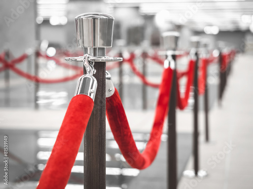 Leinwanddruck Bild Red Carpet fence pole with red ropes Blurred interior background
