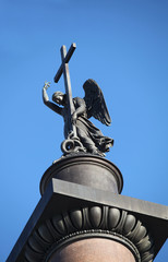 statue of winged angel with cross in blue sky