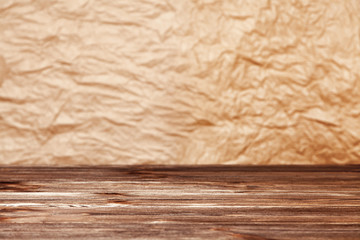 Crumpled paper background and wooden table surface