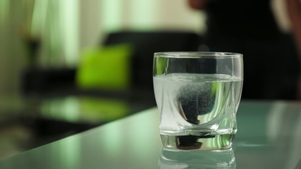 Sick Woman Puts Effervescent Tablet Aspirin In Glass Of Water