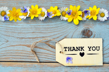 wooden background with thank you label and field flowers