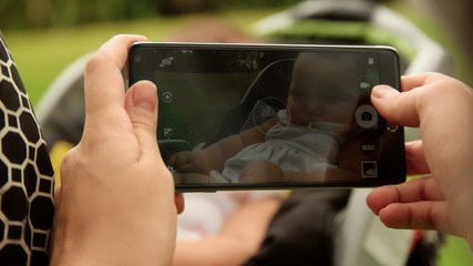 Mother Shoots Picture To Baby In Pushchair With Phone