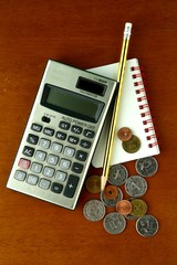 Coins, calculator, pencil and notebook