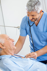 Smiling Male Caretaker Examining Senior Man