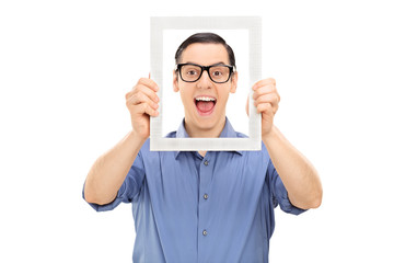 Excited young guy posing behind a picture frame