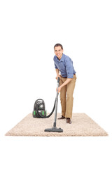 Young man cleaning with a vacuum cleaner