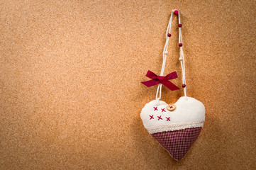 Handmade heart cloth hanging on the side of a cork board
