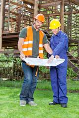 Confident Architect With Colleague Explaining Blueprint At Site