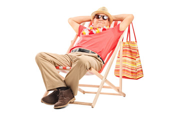 Senior gentleman sitting in a sun lounger chair