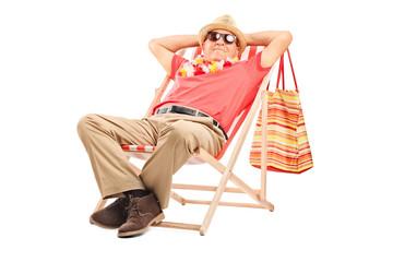 Senior gentleman sitting in a sun lounger chair