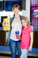 Mother And Daughter Holding Popcorn And Drink In Cinema