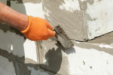 Bricklayer man worker installing block with trowel
