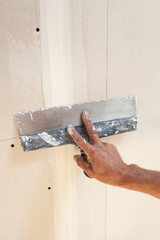 Man hand with trowel plastering a plasterboard
