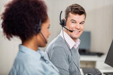 Customer Service Representative Talking With Female Colleague In