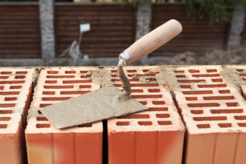 Building trowel on a red brick