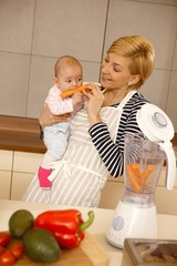 Baby eating carrot with mother