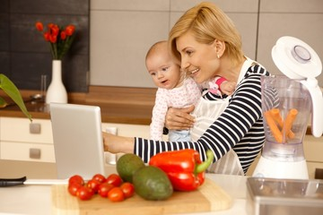 Mother and baby using laptop in kitchen
