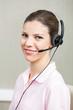 Smiling Female Call Center Employee Using Headphones