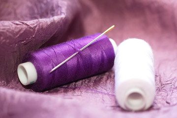 Needle and spools of thread on color textile
