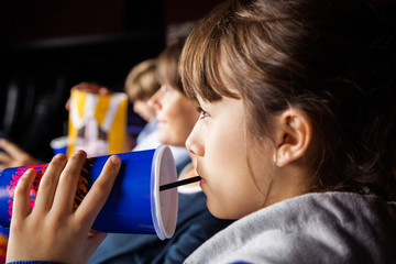 Girl Drinking Cola While Watching Movie In Theater