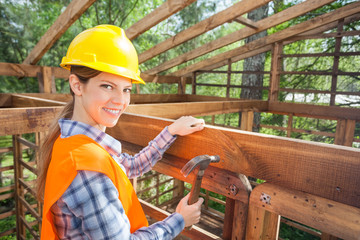 Happy Female Worker Hammering Nail On Timber Frame