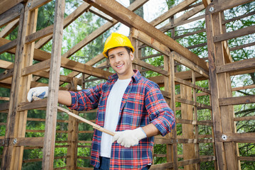 Happy Carpenter Holding Measure Tape At Construction Site