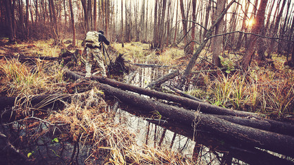 man photographer in camouflage on the  swamp