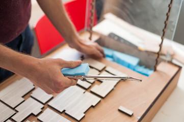 Student hands making architectural model in university studio