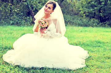 happy bride sits on a green meadow with a bouquet of flowers
