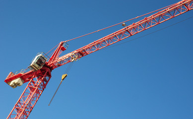 Red industrial construction crane above blue sky background
