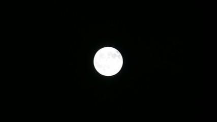 Яркая луна ночью в дымке облаков.