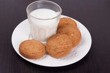 glass of milk and oat cookies on a plate