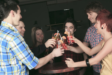 A group of friends drink on hand have some fun