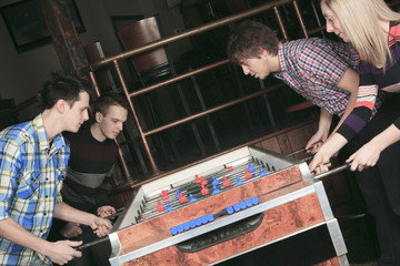 Some friends play soccer table in a bar.