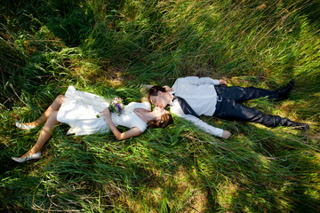 Man and women lying green grass kissing. Wedding couple in love